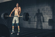 Man weight training lifting barbell in gym - ISF11443