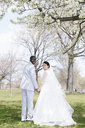 Bride and bridegroom underneath blossom covered tree, looking over shoulder at camera smiling - ISF11452