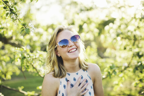 Head and shoulders of young woman wearing sunglasses, hand on chest looking at camera laughing - ISF11527