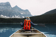 Rear view of mid adult woman paddling canoe, Moraine lake, Banff National Park, Alberta Canada - ISF11650