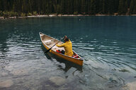 High angle rear view of mid adult man paddling canoe on Moraine lake, Banff National Park, Alberta Canada - ISF11689