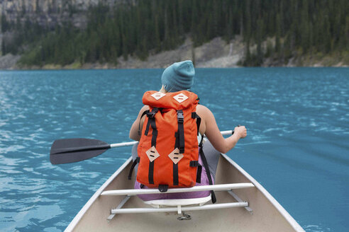Rear view of mid adult woman with orange colour backpack paddling canoe, Moraine lake, Banff National Park, Alberta Canada - ISF11695