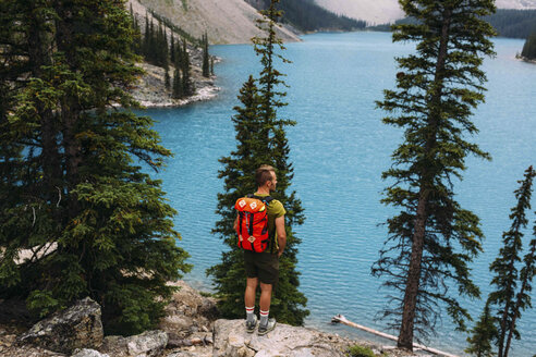 Rear view of mid adult man standing on cliff edge looking at elevated view of Moraine lake, Banff National Park, Alberta Canada - ISF11701