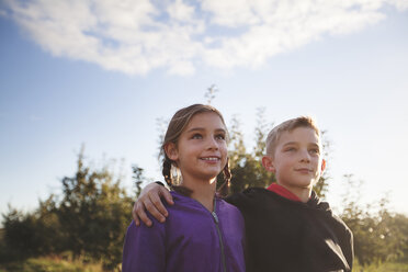 Low angle view of boy outdoors with arms around girl looking away smiling - ISF11713
