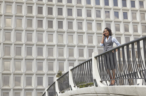 Business woman standing behind railings in front of built structure, using smartphone to make call - ISF11737
