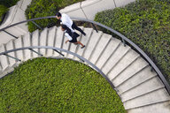 High angle view of business people ascending spiral stairway - ISF11740