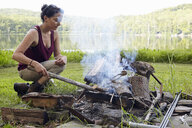 Female hiker making a campfire on lakeside, New Milford, Pennsylvania, USA - ISF11845