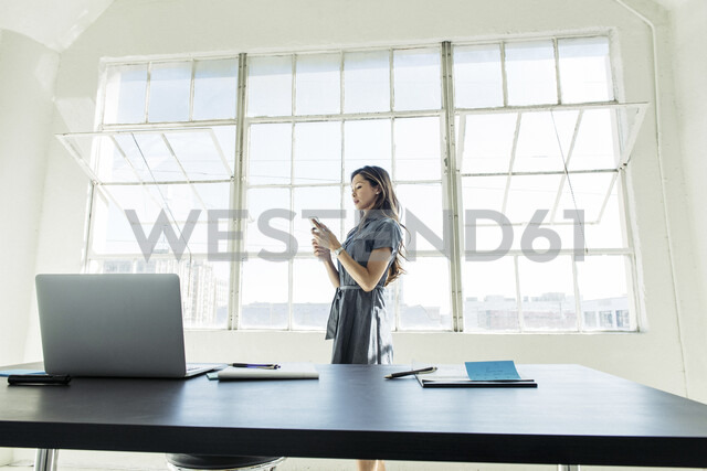 Businesswoman using smartphone by office window - ISF12025