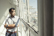 Businessman looking out of office window - ISF12031