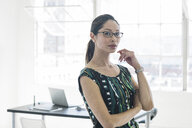 Bespectacled businesswoman in patterned dress by office window - ISF12034