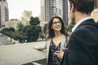 Businessman and woman talking in city, Los Angeles, USA - ISF12061