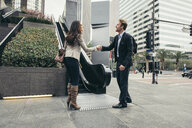 Businessman and woman shaking hands in city - ISF12064