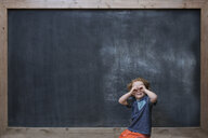 Young boy standing in front of blackboard, making glasses with hands - ISF12190