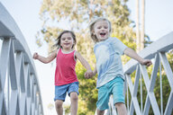 Young boy and girl walking over wooden footbridge, low angle view - ISF12196