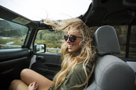Young woman with windswept long blond hair on the road in jeep - ISF12229