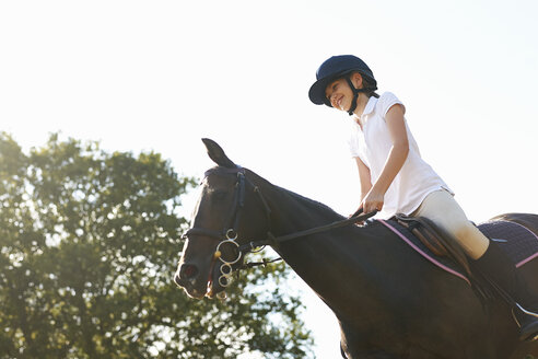 Low angle view of girl riding horse in countryside - ISF12292