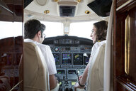 Rear view of male and female pilots talking in cockpit of private jet - ISF12388