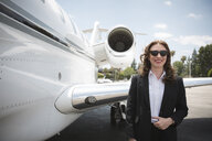 Portrait of mid adult female businesswoman and private jet at airport - ISF12400