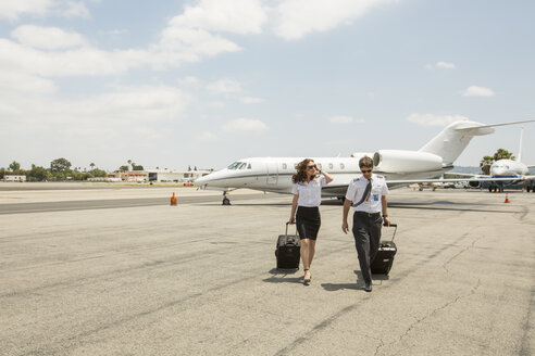 Male and female private jet pilots arriving at airport - ISF12406
