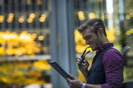 Happy young businessman leaning against park window reading digital tablet - ISF12637