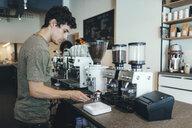 Barista preparing coffee in a coffee bar - OCAF00311