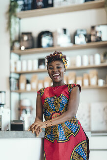 Portrait of happy woman in a coffee bar - OCAF00314