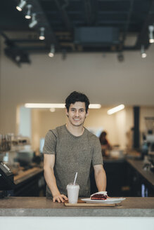 Portrait of smiling man serving drink and cake in a coffee bar - OCAF00317