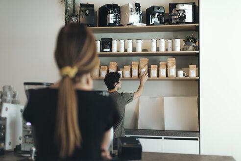 Man selling coffee in a coffee bar - OCAF00329