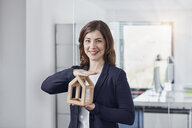 Portrait of smiling young businesswoman holding architectural model in office - RORF01259