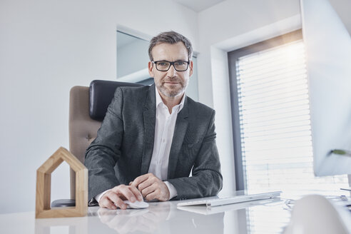 Portrait of businessman at desk in office with architectural model - RORF01262