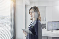 Smiling young businesswoman with tablet looking out of window in office - RORF01268