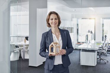 Portrait of smiling businesswoman holding architectural model in office - RORF01271