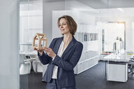 Smiling businesswoman looking at architectural model in office - RORF01274