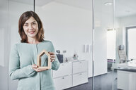 Portrait of smiling young businesswoman holding architectural model in office - RORF01283