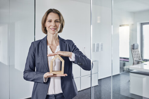 Portrait of businesswoman holding architectural model in office - RORF01286