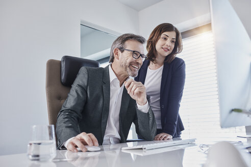 Smiling businessman and businesswoman looking at computer at desk in office - RORF01289