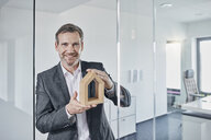 Portrait of smiling businessman holding architectural model in office - RORF01298