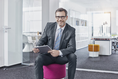 Portrait of smiling businessman using tablet in office - RORF01301