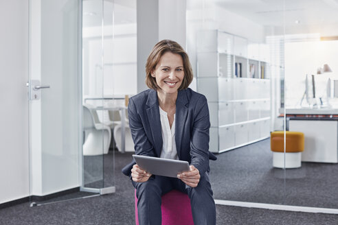 Portrait of smiling businesswoman using tablet in office - RORF01304