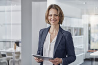 Portrait of smiling businesswoman holding tablet in office - RORF01307
