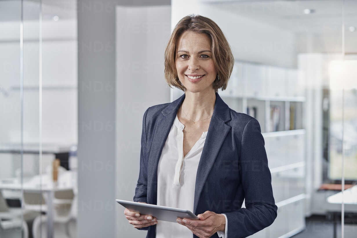 Portrait of smiling businesswoman holding tablet in office - RORF01307 - Roger Richter/Westend61