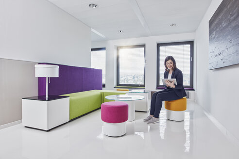 Young businesswoman using tablet in office lounge - RORF01319