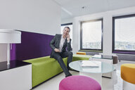 Happy businessman on smartphone in office lounge - RORF01325