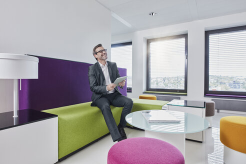 Happy businessman with tablet in office lounge - RORF01328