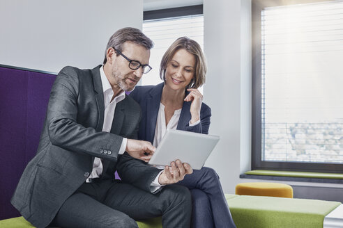 Smiling businessman and businesswoman using tablet in office lounge together - RORF01331