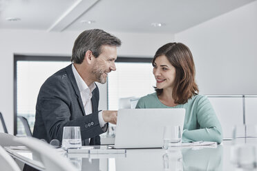Businessman and businesswoman having a meeting in office with laptop - RORF01334