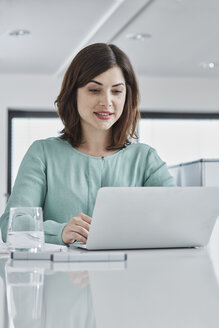 Young businesswoman using laptop at desk in office - RORF01340