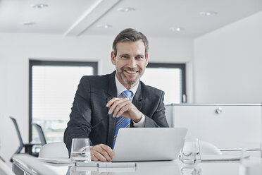 Portrait of smiling businessman with laptop at desk in office - RORF01343