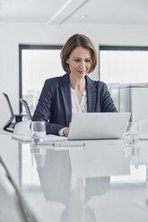 Businesswoman using laptop at desk in office - RORF01346