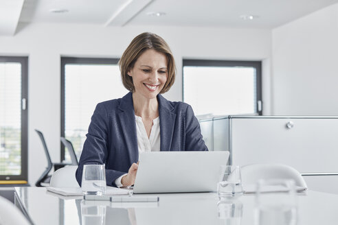 Smiling businesswoman using laptop at desk in office - RORF01349